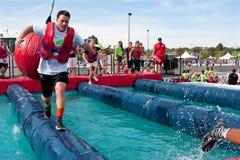 Courses d'homme en détruisant des boules à la course d'obstacle folle Images stock