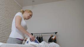 Courses de femme au foyer de femme chemise blanche et danses avec du fer dans des ses mains banque de vidéos