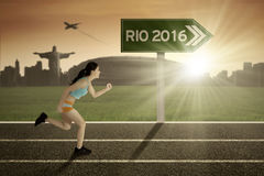 Courses de femme avec le poteau indicateur de Rio 2016 Photo stock
