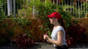 Courses de femme en bas de la rue parmi les palmiers Mode de vie actif sain Mouvement lent banque de vidéos