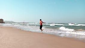 Courses de jeune homme le long de bord de la mer Plage d'été Concept de liberté Mâle européen appréciant des vacances de vacances clips vidéos