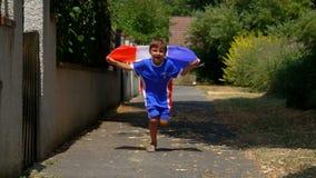 Courses joyeuses de garçon avec le drapeau français dans des ses mains banque de vidéos
