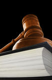 Court gavel. Judge's court gavel on a law book, on black Stock Photography