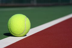 On the court line. Tennis ball on the court line dividing two colors of the court Royalty Free Stock Image