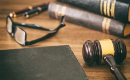 Law or auction gavel and a book, wooden office desk background. Closeup view, space for text stock images