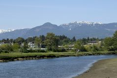 Courtenay river view towards the mountains. Nature scene at the Courtenay estuary, looking across the Courtenay river towards the snow capped Strathcona Mountain stock image