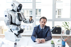 Courteous android is giving espresso for businessman. Busy at work. Caring robot is holding cup of coffee for senior manager, who is sitting at desk with laptop Stock Photo