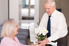 Courteous gentleman holding a bouquet. Nice present. Pleasant good looking suave men giving his lady flowers to celebrate their love while she sitting at the Royalty Free Stock Images