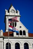 Courthouse. Verticle shot of courthouse clock tower with american and missouri flags against clear dark blue sky stock photos