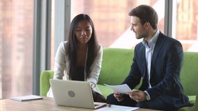 Courtier asiatique féminin de directeur consultant le client masculin caucasien avec l'ordinateur portable banque de vidéos