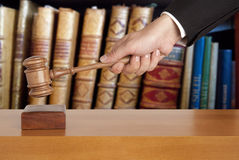 Courtroom. Gavel in hand against the background of the courtroom stock image