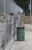 Between the Courts. A concrete pathway leads between the various courts of a park, accompanied by wood ties, a chain-link fence, and a rusty green garbage bin Royalty Free Stock Photos