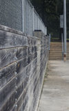 Between the Courts II. A concrete pathway leads between the various courts of a park, accompanied by wood ties, and a chain-link fence Stock Images