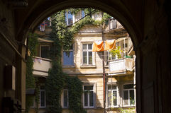 Courtyard Through Arch. Old residential house courtyard viewed through architectural arch Royalty Free Stock Images