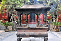 Courtyard and censer in Chinese temple. Courtyard and an old censer in Chinese temple, surround with traditional architecture and trees Royalty Free Stock Photo