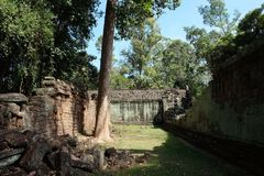 The courtyard of the dilapidated temple complex in Indochina. Ancient ruins in the forest.  stock photo