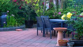 Courtyard garden setting. Beautiful springtime Mediterranean style courtyard garden with outdoor setting Royalty Free Stock Photo