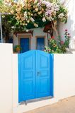 Courtyard Gates. Beautiful old blue gates with Yellow, Pink and Red flowers Royalty Free Stock Photos