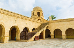 The courtyard of the Grand Mosque. SOUSSE, TUNISIA - SEPTEMBER 6, 2015: The stone courtyard of the Grand Mosque with the long arcades on each side and the tiny Royalty Free Stock Photo