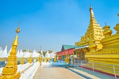 The way to the shrine of Kuthodaw Pagoda, Mandalay, Myanmar. The courtyard of Kuthodaw Pagoda complex with high carved golden pagoda with entrance to the shrine royalty free stock images