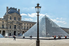 The courtyard of the Louvre with glass piramid and old lantern in Paris on a sunny day Stock Image