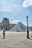 The courtyard of the Louvre with glass piramid and old lantern in Paris on a sunny day Stock Photos