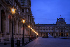 Courtyard of the Louvre Museum in Paris. Very early on an overcast morning Royalty Free Stock Image