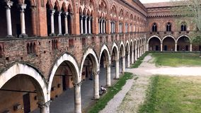 Courtyard of a medieval castle with an architectural row of columns and arches. Pavia, Italy stock video