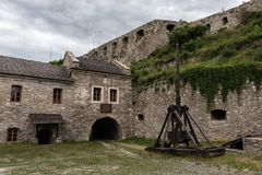 The courtyard of the medieval fortress with the idle old trebuchet. Complex of defensive buildings, XVI-XVIII centuries. Kamianets-Podilskyi, Ukraine stock photography