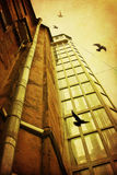 Courtyard with old glass elevator shaft and flying birds Royalty Free Stock Photo
