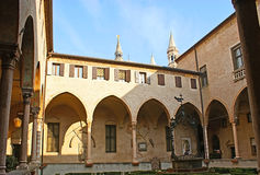 The courtyard. PADUA, ITALY - FEBRUARY 24, 2012: The cozy courtyard of the Basilica of Saint Anthony of Padua with a small garden, surrounded by shady arcades Stock Photos