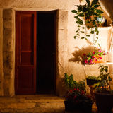 Courtyard with plants at night. An open door and plants in a small courtyard at night Stock Image