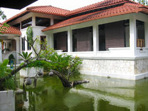 Courtyard with pond and white house under tile roof. The courtyard with the pond and white house under the brown tile roof (paddi museum, Malaysia Stock Image