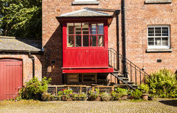 Courtyard with redbrick house and iron steps leading to a red po Stock Photography