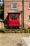 Courtyard with redbrick house and iron steps leading to a red po Stock Images
