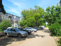 Courtyard of the road , cars , trees, and houses in the city Stock Photography