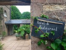 Courtyard sign reading. A courtyard is visible next to a stone building. In the foreground, a sign reads hotel & restaurant Stock Photo