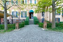 Decorative courtyard garden at villa in Italy. Courtyard with trees and lion statues in an Italian palazzo in Siena, Italy, in horizontal orientation royalty free stock photo