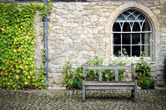 Courtyard. A wooden bench in a courtyard with cobbled stones Royalty Free Stock Image