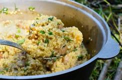 Cous cous för läcker havregröt med kött, grönsaker och nya örter i en krukamatlagning på naturen royaltyfri bild