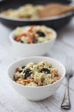 Couscous in a bowl. Cosucous cooked with vegetables, olives, carots, and spice in a bowl Stock Photos