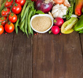 CousCous in a bowl and fresh vegetables. On wood Stock Photography
