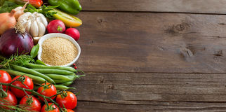 CousCous in a bowl and fresh vegetables. On wood Stock Image