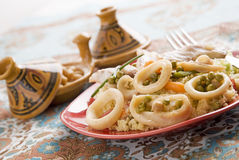 Couscous fish. Fish  with couscous, garnished with spring potatoes carrots and green peas Stock Photo