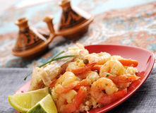 Couscous fish. Fish  and shrimps with couscous, garnished with  carrots and green peas Stock Photos