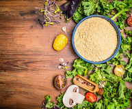 Couscous with fresh kale  and vegetables ingredients for cooking on rustic wooden background, top view Stock Photography