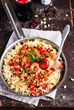 Couscous with fried prawns, mixed vegetables, pine nuts served in a cooking pan on a wooden table, selective focus. Traditional ea. Stern meal. Summer picnic stock image