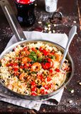 Couscous with fried prawns, mixed vegetables, pine nuts served in a cooking pan on a wooden table, selective focus. Traditional ea. Stern meal. Summer picnic stock photo