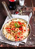 Couscous with fried prawns, mixed vegetables, pine nuts served in a cooking pan on a wooden table, selective focus. Traditional ea. Stern meal. Summer picnic royalty free stock image