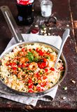 Couscous with fried prawns, mixed vegetables, pine nuts served in a cooking pan on a wooden table, selective focus. Traditional ea. Stern meal. Summer picnic royalty free stock images